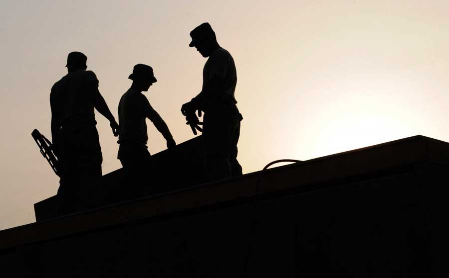 silhouette of Construction men on house - building permit expediters are needed